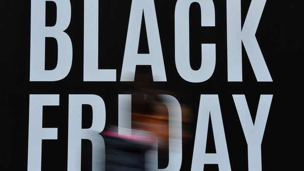 Shoppers pass a promotional sign for 'Black Friday' sales discounts in London, on November 23, 2018. - Black Friday is a sales offer originating from the US where retailers slash prices on the day after the Thanksgiving holiday. In the UK it is used as a marketing device to entice Christmas shoppers with the discounts at stores often lasting for a week. (Photo by Ben STANSALL / AFP)        (Photo credit should read BEN STANSALL/AFP/Getty Images)