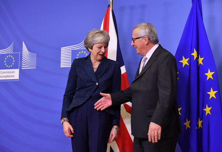 European Commission President Jean-Claude Juncker, right, reaches out to shake hands with British Prime Minister Theresa May