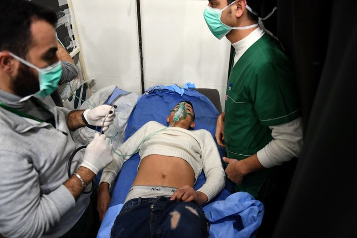A man breathes through an oxygen mask inside a hospital after what the Syrian state media said was a suspected toxic gas atta