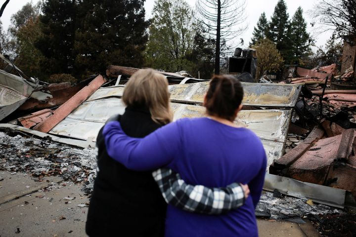 Irma Corona (R) comforts neighbor Gerryann Wulbern in front of the remains of Wulbern's home after the two returned for the f