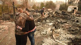 Kimberly Spainhower hugs her daughter Chloe, 13, while her husband Ryan Spainhower (R) searches through the ashes of their burned home in Paradise, California on November 18, 2018. (Photo by Josh Edelson / AFP)        (Photo credit should read JOSH EDELSON/AFP/Getty Images)