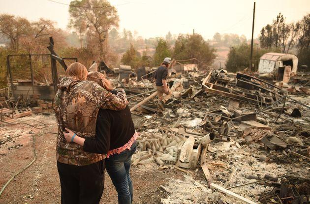 Kimberly Spainhower hugs her daughter Chloe, 13, while her husband Ryan Spainhower searches through the...