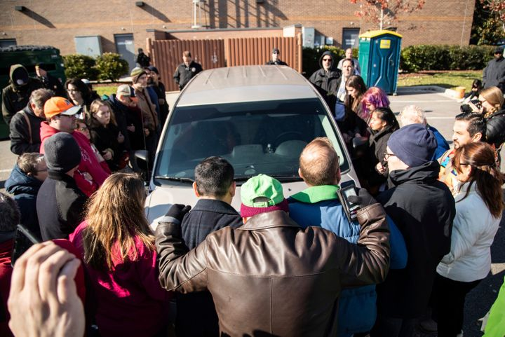 Demonstrators surround a government vehicle after Samuel Oliver-Bruno, 47, an undocumented Mexican national, was arrested Fri