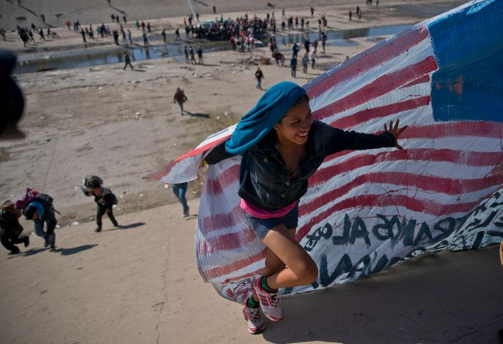 A migrant woman helps carry a handmade U.S. flag up the riverbank at the Mexico-U.S. border after getting past Mexican police