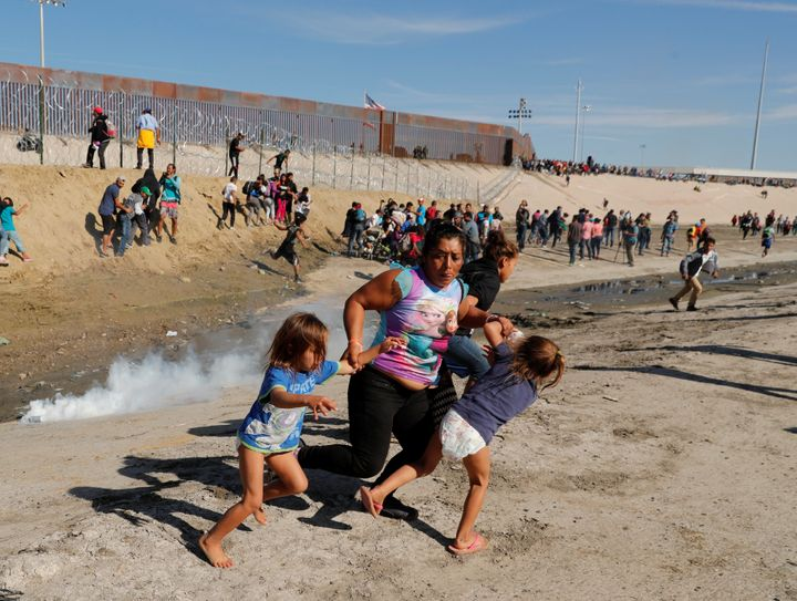 Maria Lila Meza Castro, a 39-year-old from Honduras, part of a caravan of thousands of Central Americans trying to reach the United States, runs from tear gas with her 5-year-old twins, Saira Nalleli Mejia Meza, left, and Cheili Nalleli Mejia Meza, at the U.S.-Mexico border in Tijuana on Nov. 25.