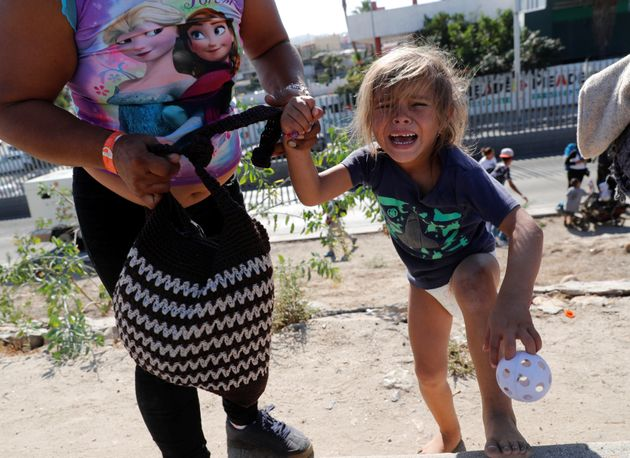 A Honduran toddler in diapers who came to the border on the migrant caravan sobs after she and her mother...