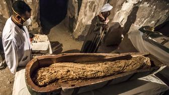This picture taken on November 24, 2018 shows Egyptian workers and archaeologists standing next to an opened intact sarcophagus containing a well-preserved mummy of a woman named 'Thuya' wrapped in linen, discovered by a French mission at the site of Tomb TT33 which dates to the 18th dynasty (16th-13th century BC) at Al-Assasif necropolis on the west bank of the Nile north of the southern Egyptian city of Luxor. - Located between the royal tombs at the Valley of the Queens and the Valley of the Kings, the Al-Assasif necropolis is the burial site of nobles and senior officials close to the pharaohs. (Photo by Khaled DESOUKI / AFP)        (Photo credit should read KHALED DESOUKI/AFP/Getty Images)