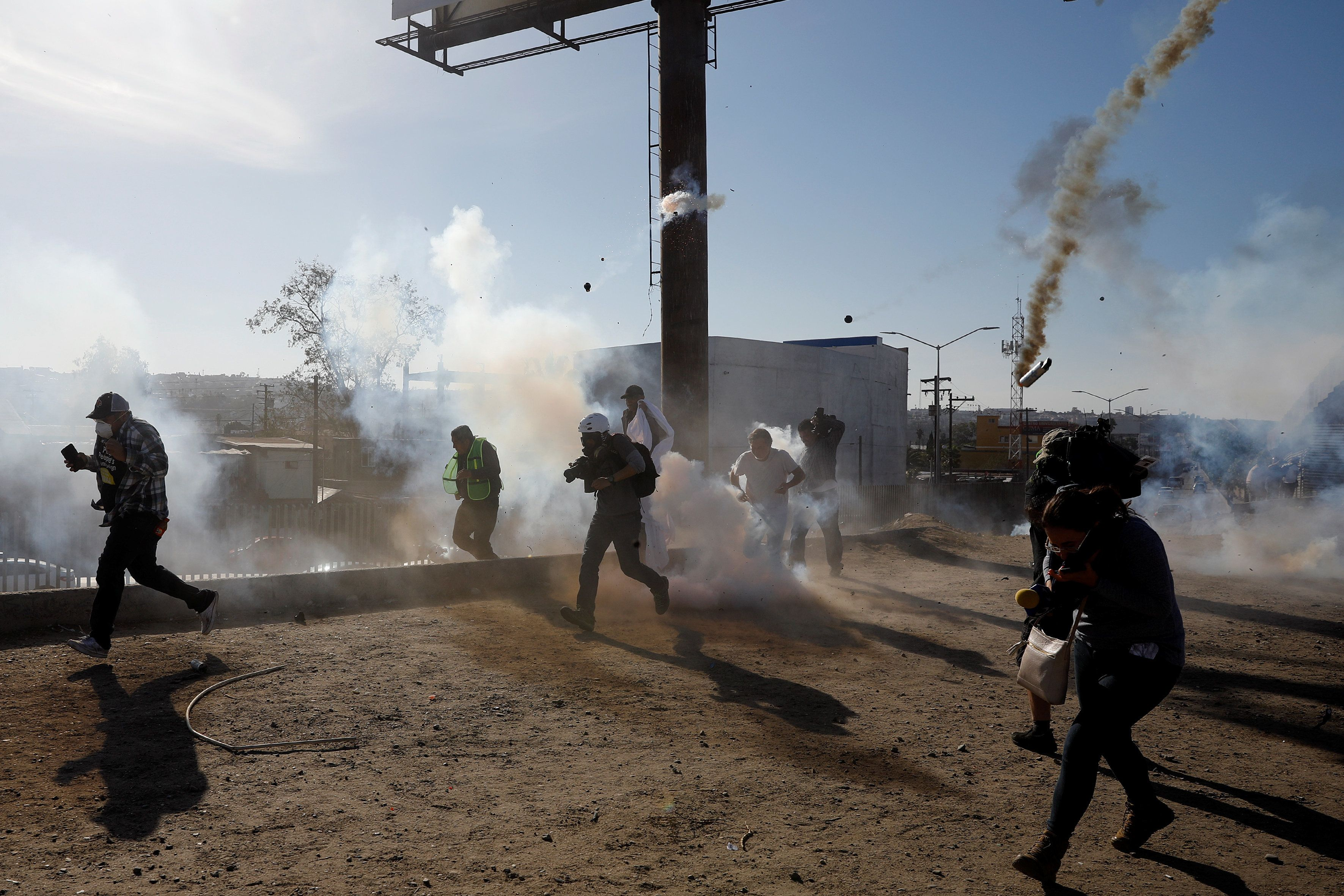 Migrants, part of a caravan of thousands traveling from Central America en route to the United States, and journalists flee t