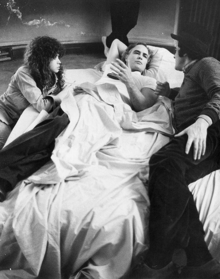 American actor Marlon Brando (center) with actress Marie Schneider (left) and Bernardo Bertolucci (right) in Bertolucci's fil