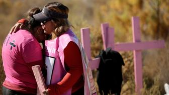 Relatives of missing women react next to wooden crosses at El Navajo creek, where the bodies of several women were found, during a ceremony to mark the International Day for the Elimination of Violence Against Women in Praxedis G. Guerrero, on the outskirts of Ciudad Juarez, Mexico, November 24, 2017. REUTERS/Jose Luis Gonzalez