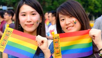 TAIPEI, TAIWAN - 2018/11/18: Two young women at the LGBT organized rally in downtown Taipei holding rainbow flags in support to  same sex marriage which was legalized in Taiwan in 2017. However a referendum on some unsolved issue related to to gay and lesbian couples is to be held on November 24th where voters will have to answer several questions with a yes or a no. (Photo by Alberto Buzzola/LightRocket via Getty Images)