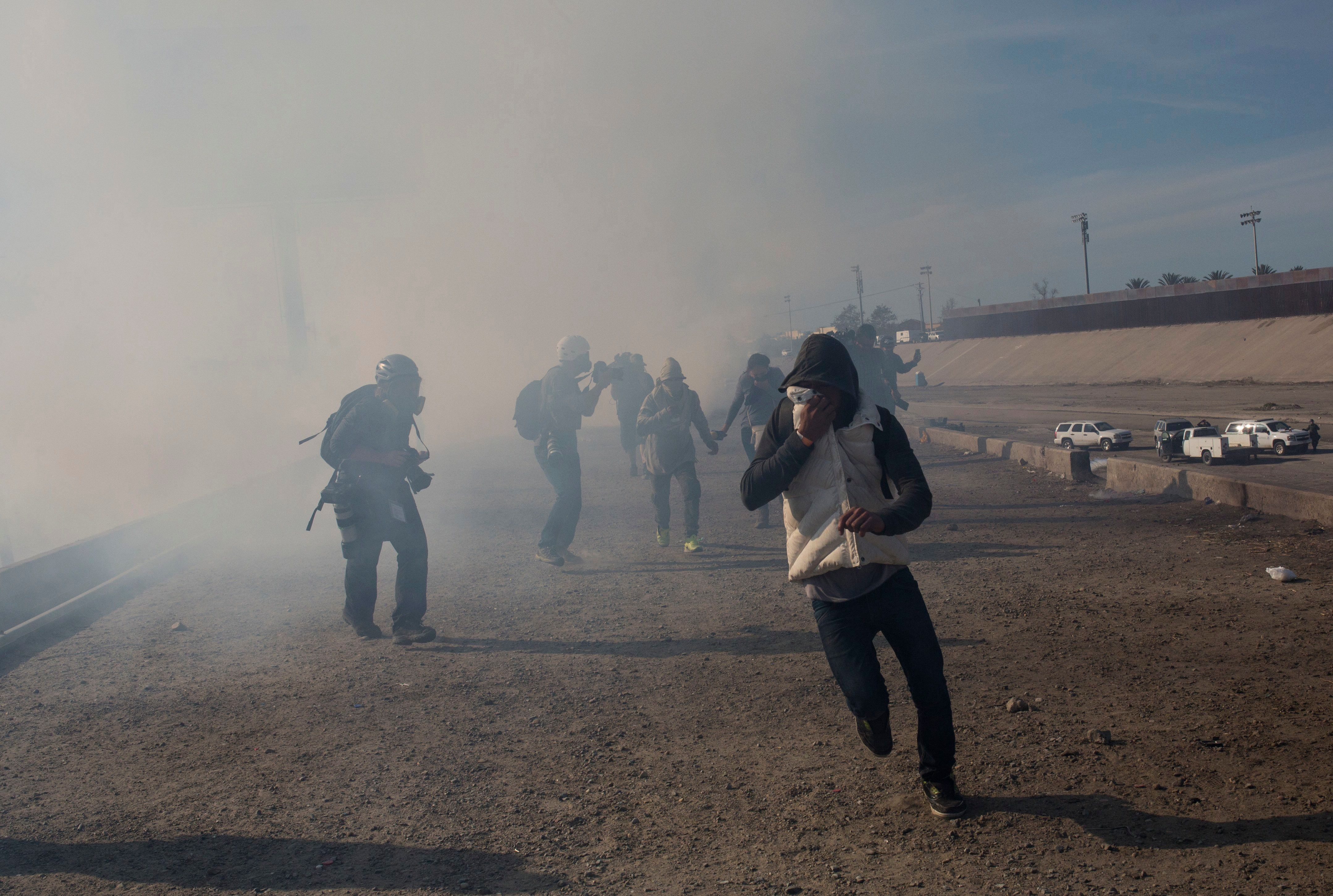 Migrants run from tear gas launched by U.S. agents, amid photojournalists covering the Mexico-U.S. border, after a group of m