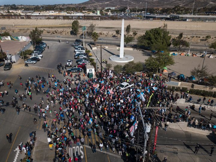 A group of migrants gather at the Chaparral border crossing in Tijuana, Mexico, Sunday, Nov. 25, 2018, as they try to pressur