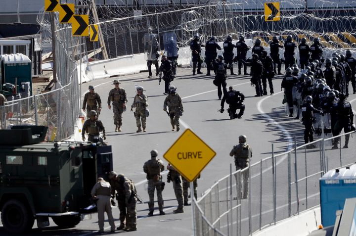 Military personnel and Customs and Border Protection officers gather along the southbound lanes of the San Ysidro port of ent