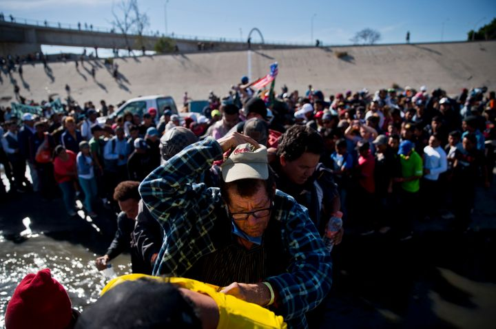 Migrants cross the river at the Mexico-U.S. border after pushing past a line of Mexican police at the Chaparral crossing in T