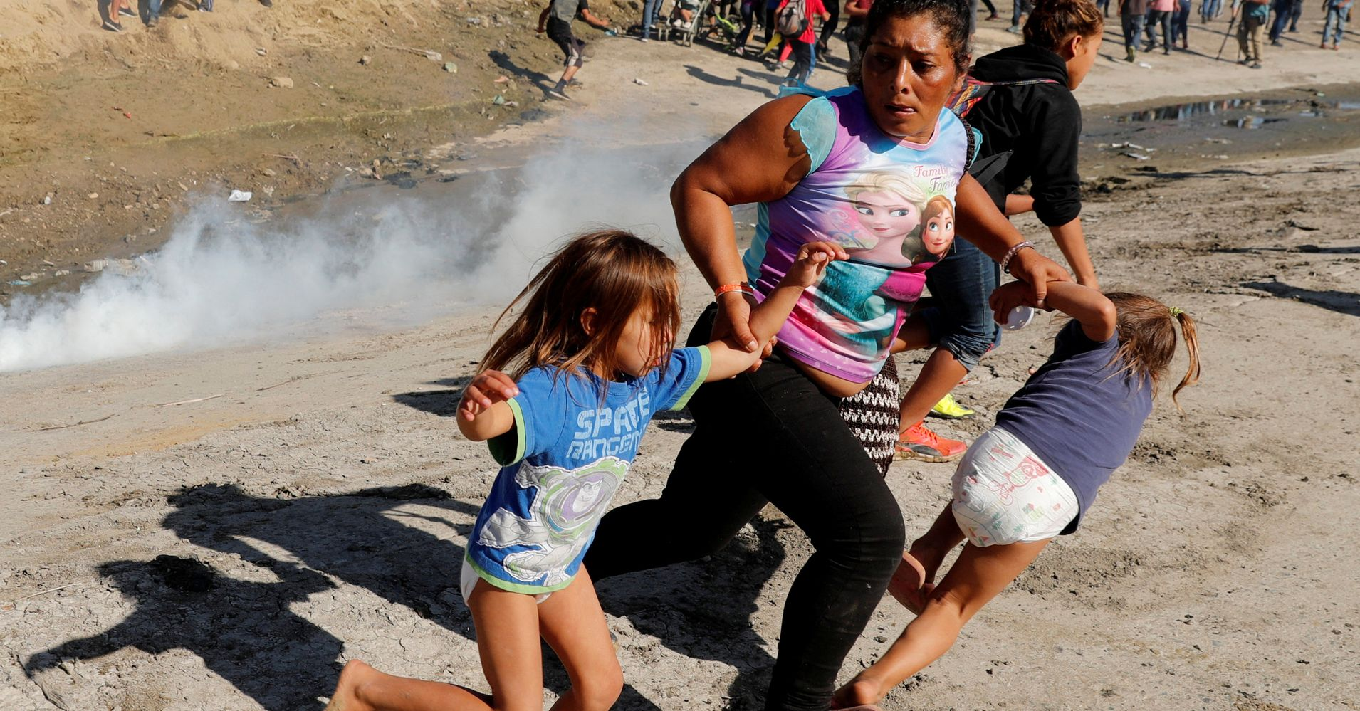 Image result for migrant child fence cage tear gas fleeing