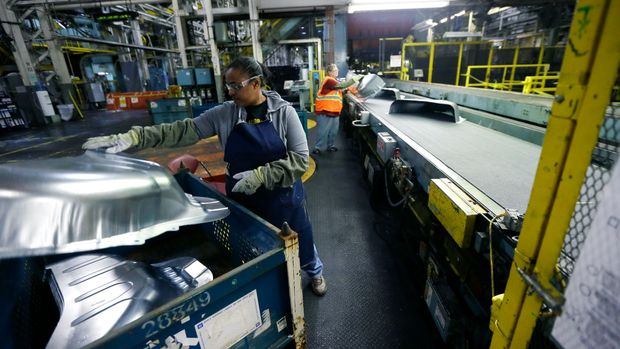 FILE - In this April 30, 2015, file photo, United Auto Workers line worker Michelle Albritton loads stamped wheel housings at the General Motors Pontiac Metal Center in Pontiac, Mich. United Auto Workers union has reached a tentative contract agreement with Ford on Friday, Nov. 6, 2015, a sign that union leaders expect General Motors workers to approve a similar four-year deal. Voting at GM plants was scheduled to end Friday evening. (AP Photo/Carlos Osorio, File)