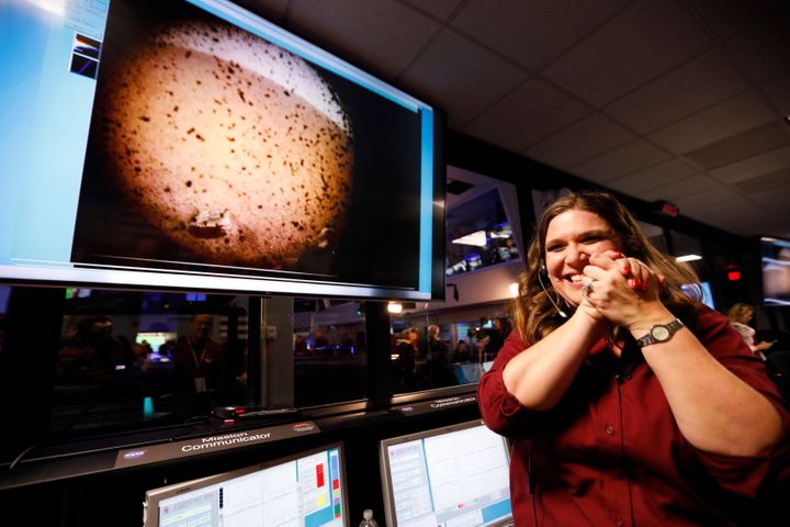 An engineer smiles next to an image of Mars sent from the InSight lander shortly after it landed on Mars.