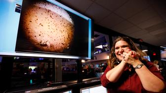 An engineer smiles next to an image of Mars sent from the InSight lander shortly after it landed on Mars in the mission support area of the space flight operation facility at NASA's Jet Propulsion Laboratory Monday, Nov. 26, 2018, in Pasadena, Calif. (Al Seib/Los Angeles Times via AP, Pool)