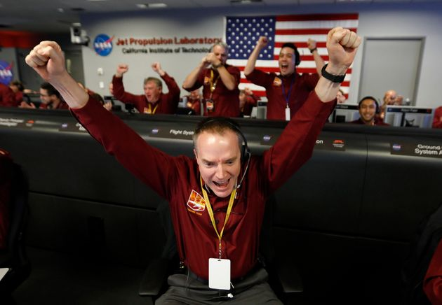 Engineer Kris Bruvold, bottom center, celebrates as the InSight lander touch downs on
