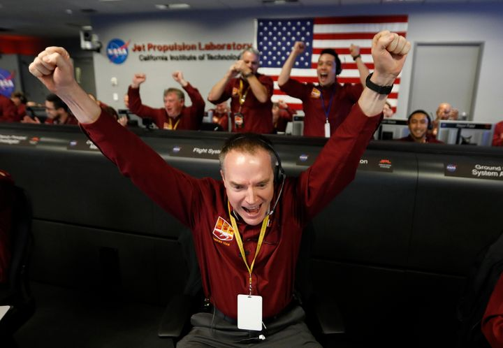 Engineer Kris Bruvold, bottom center, celebrates as the InSight lander touch downs on Mars.
