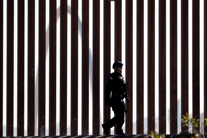 A U.S. Customs and Border Protection Special Response Team officer walks along a border wall, as the Monumental Arch in Tijua