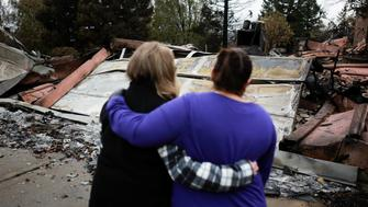 Irma Corona (R) comforts neighbor Gerryann Wulbern in front of the remains of Wulbern's home after the two returned for the first time since the Camp Fire in Paradise, California, U.S. November 22, 2018.  REUTERS/Elijah Nouvelage     TPX IMAGES OF THE DAY