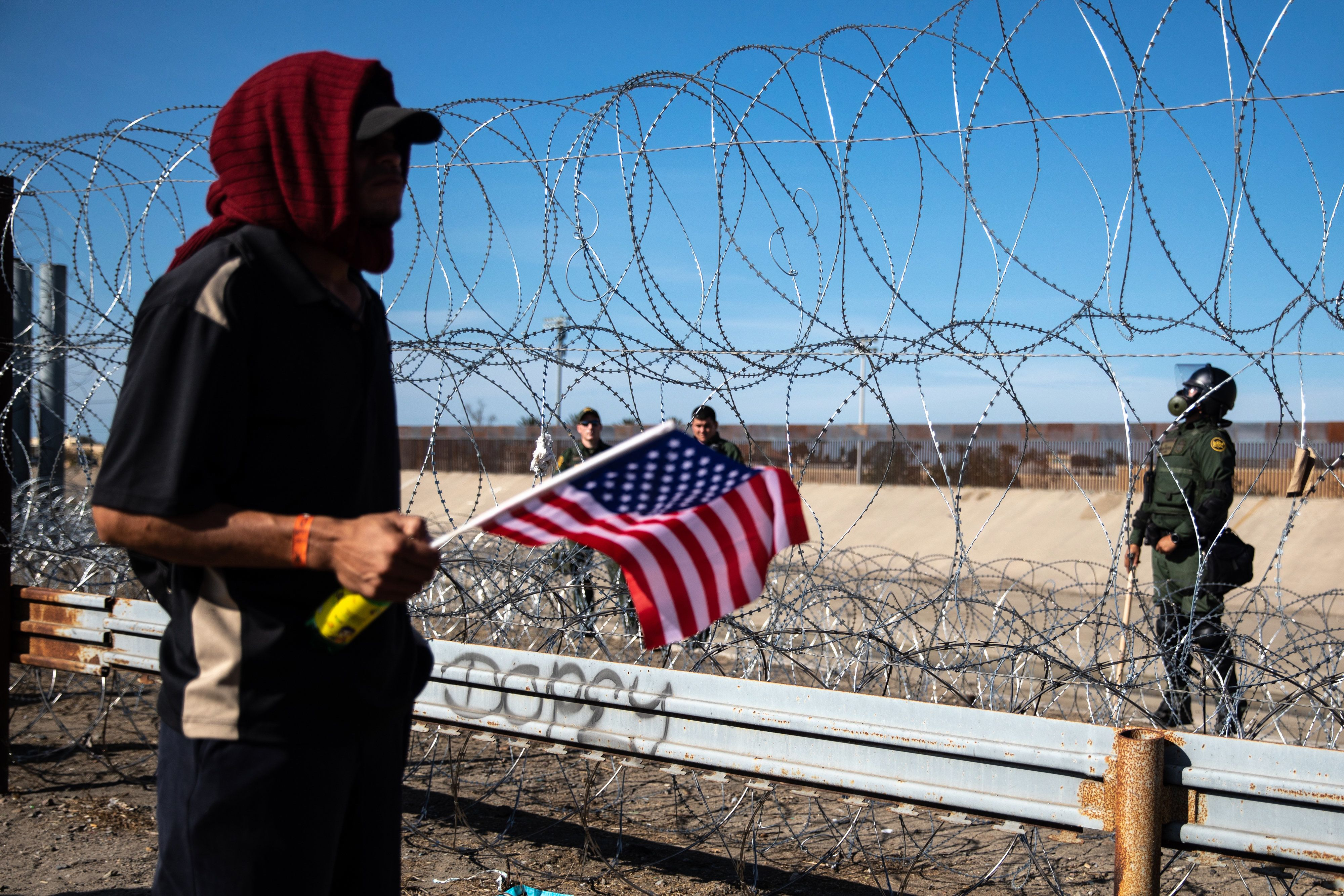 A Central American migrant holds an American flag near barbed wire border fence along the the US and Mexico border in Tijuana, Mexico, on Sunday, Nov. 25, 2018. U.S. border officials temporarily closed the San Ysidro port of entry between Tijuana and San Diego, one of the busiest border crossings in the world, 'to ensure public safety.' Photographer: Tomas Ayuso/Bloomberg via Getty Images