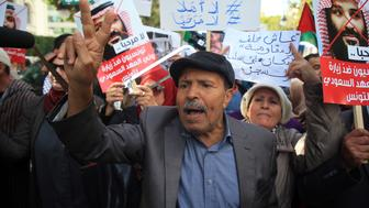 TUNIS, TUNISIA - NOVEMBER 27 : Tunisians hold up signs and flags as they protest against the expected visit of the Saudi Crown Prince to the country, in Habib Bourguiba Avenue in the capital Tunis, Tunisia on November 27, 2018. (Photo by Yassine Gaidi/Anadolu Agency/Getty Images)