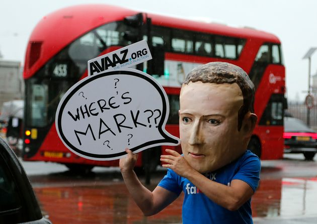 An activist wearing a Mark Zuckerburg mask stands outside the UK Parliament in
