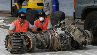 Officials inspect an engine recovered from the crashed Lion Air jet on Monday in Jakarta, Indonesia, Sunday, Nov. 4, 2018. The brand new Boeing 737 MAX 8 jet plunged into the Java Sea just minutes after takeoff from Jakarta early on Oct. 29, killing all of its passengers on board. (AP Photo/Achmad Ibrahim)