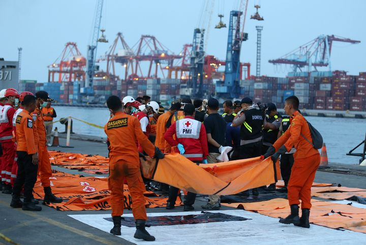 Officials examine victims recovered from the Lion Air jet that crashed into Java Sea on Monday at Tanjung Priok Port in Jakar