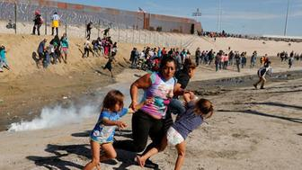 Maria Meza (C), a 40-year-old migrant woman from Honduras, part of a caravan of thousands from Central America trying to reach the United States, runs away from tear gas with her five-year-old twin daughters Saira Mejia Meza (L) and Cheili Mejia Meza (R) in front of the border wall between the U.S. and Mexico, in Tijuana, Mexico November 25, 2018. REUTERS/Kim Kyung-Hoon