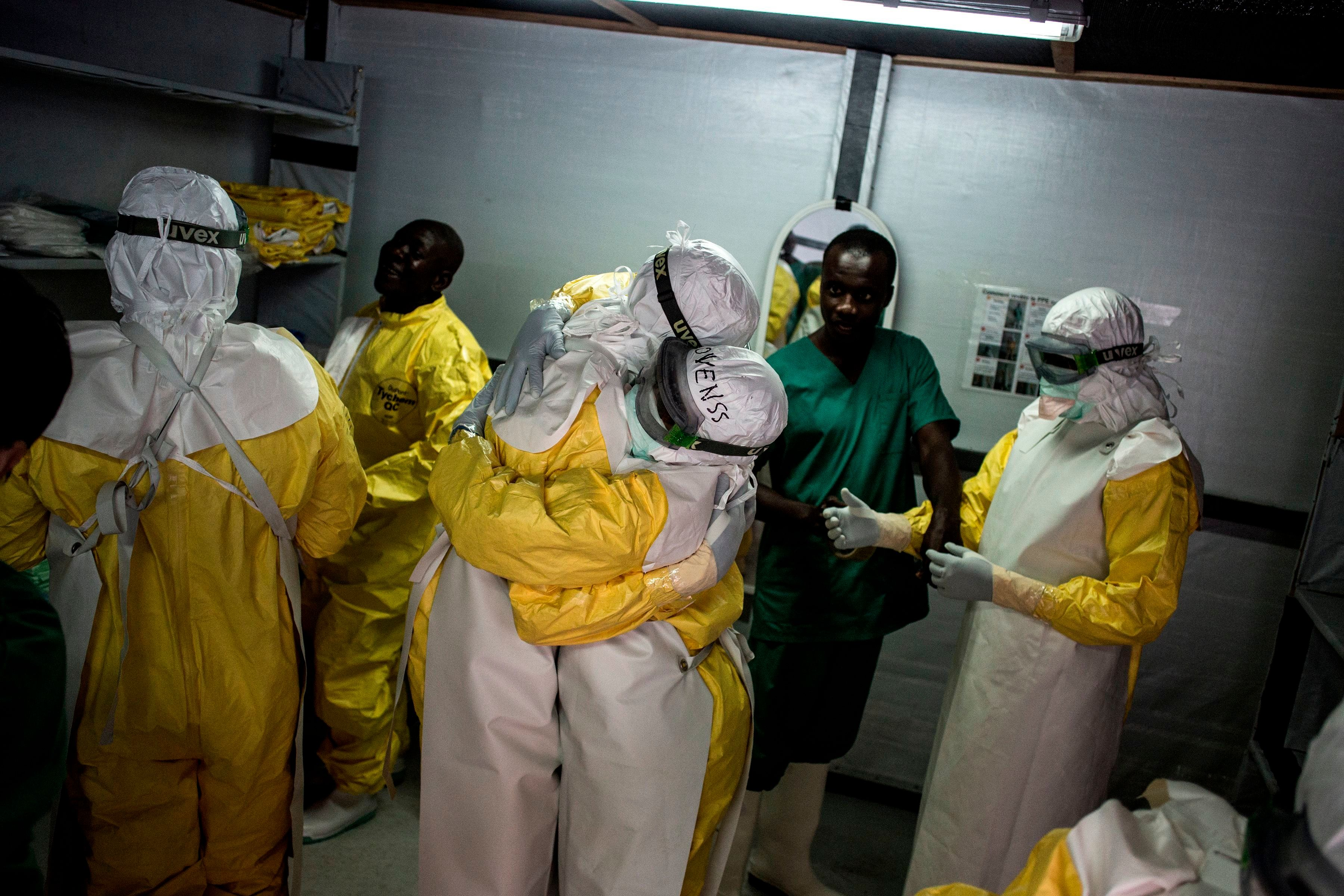 Health workers embrace whilst putting on their personal protective equipment (PPE) before heading into the red zone at a newly build MSF (Doctors Without Borders) supported ebola treatment centre (ETC) on November 7, 2018 in Bunia, Democratic Republic of the Congo. - The death toll from an Ebola outbreak in eastern Democratic Republic of Congo has risen to more than 200, the health ministry said on November 10, 2018. (Photo by John WESSELS / AFP)        (Photo credit should read JOHN WESSELS/AFP/Getty Images)