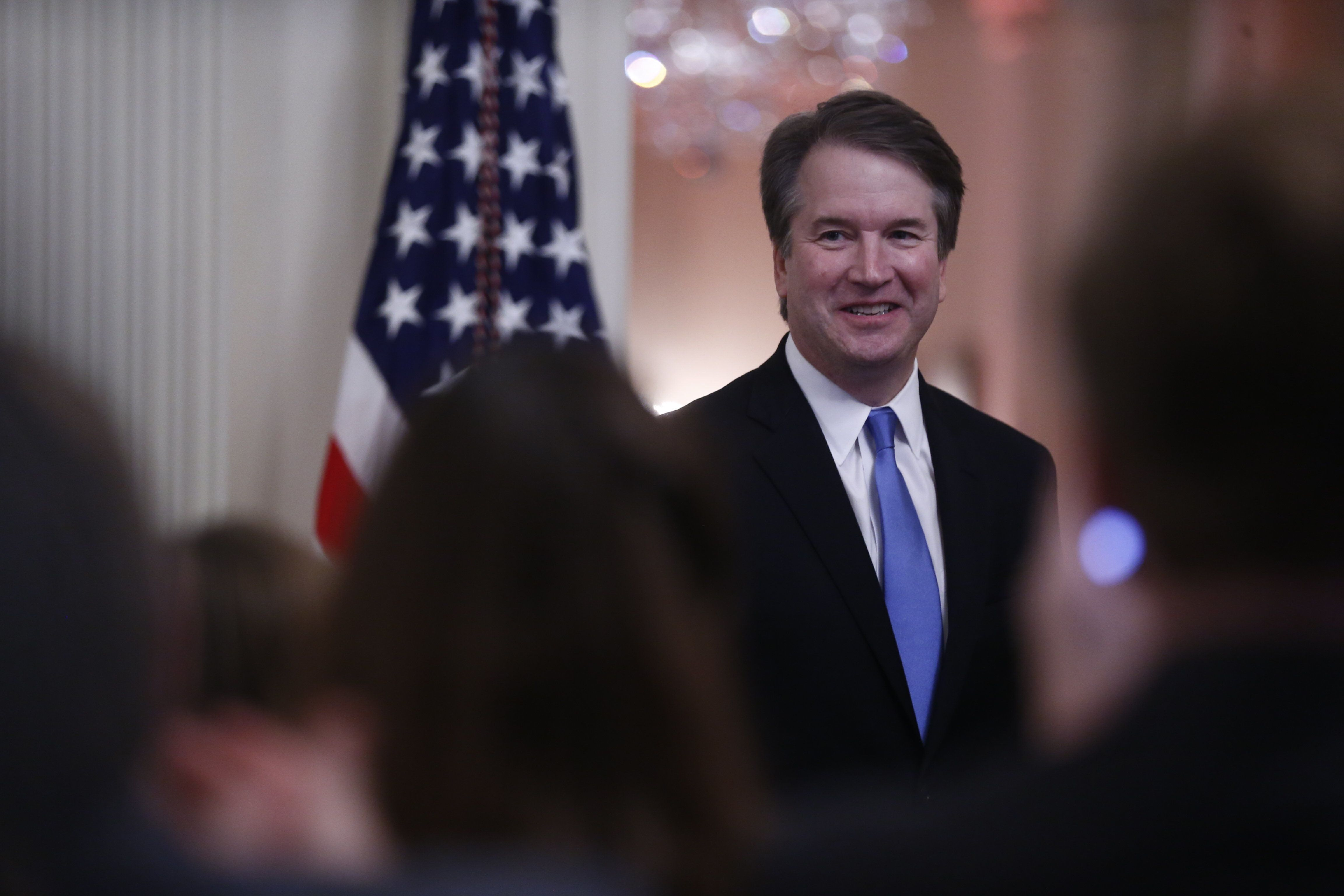 Brett Kavanaugh, associate justice of the U.S. Supreme Court, smiles as U.S. President Donald Trump speaks during a ceremonia