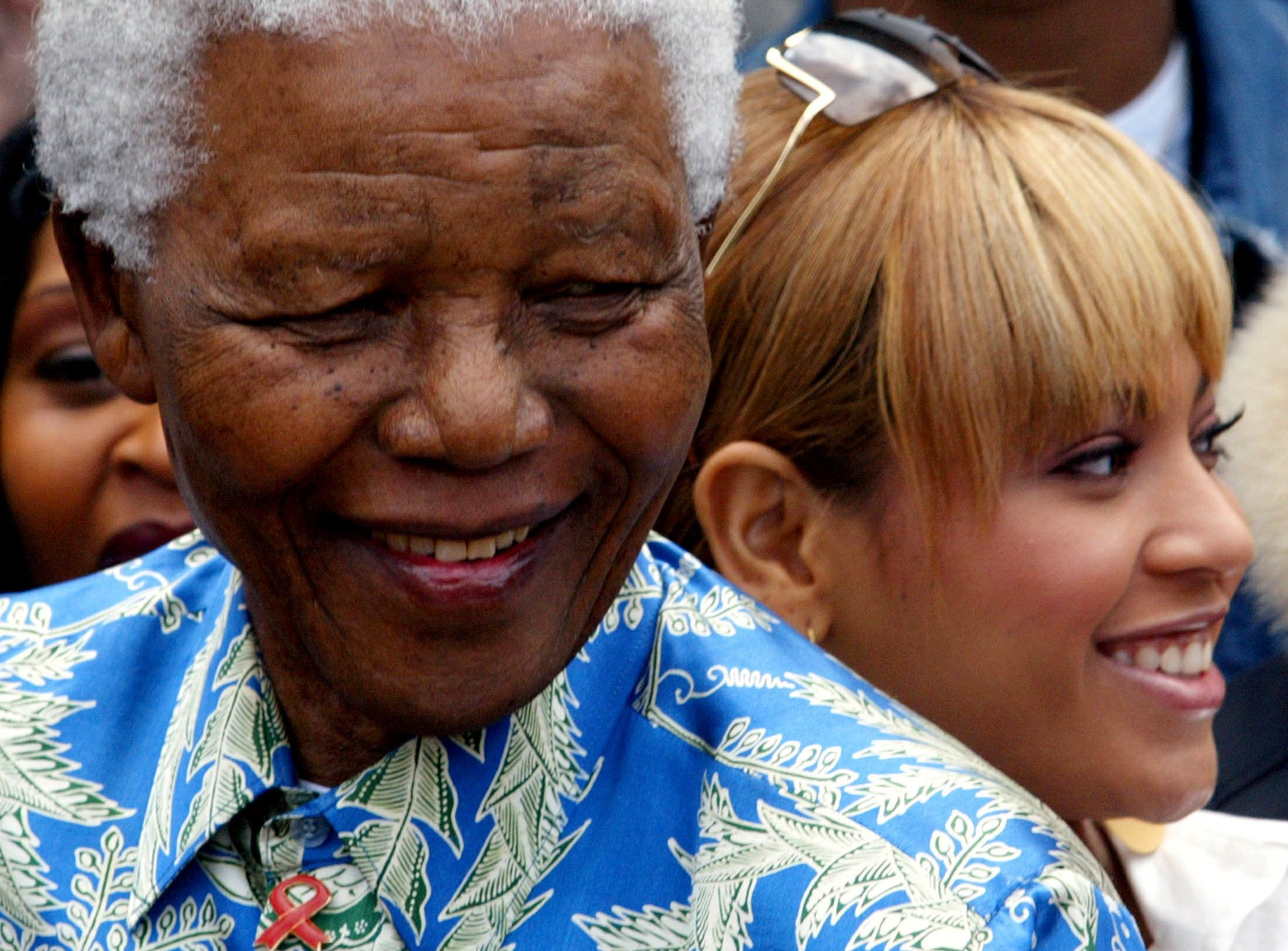 """Nelson Mandela poses for photographers with singer Beyonce Knowles (L) and other performers during a visit to Robben Island Prison near Cape Town, November 28, 2003. Knowles will perform with a host of other stars at the """"46664"""" Aids benefit concert on November 29. """"46664"""" refers to the prison number allocated to Mandela during his long incarceration on the Island. REUTERS/Mike Hutchings PP03110103  MH"""