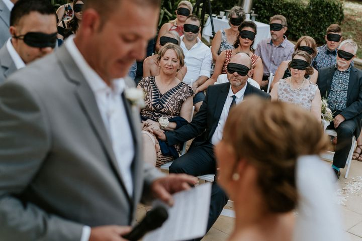Wedding guests wear black blindfolds during the ceremony. One woman in the center of the shot is not wearing a blindfold: Agnew's mom, who also has cone-rod dystrophy.In the foreground and out of focus, you can see the groom in a gray suit and the bride in a veil with her hair pulled back in a chignon.