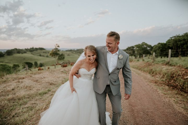 The bride and groom stand together laughing on a dirt road with green hills and a pale blue, partly cloudy sky behind them. The groom has his arm wrapped around the bride's waist as she holds her skirt in one hand.