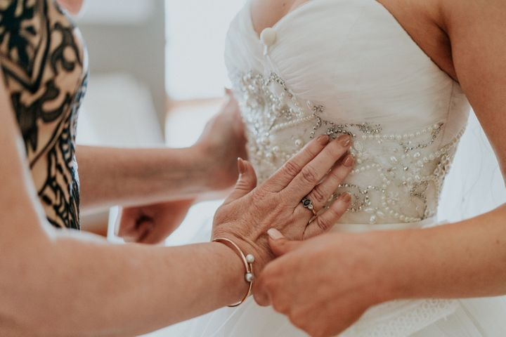 In this close-up shot, Agnew's mother uses her hands to feel the beading on the bodice of her daughter's wedding gown.
