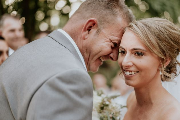 A close-up of the bride and groom's smiling faces, their foreheads touching. The groom is in profile,...