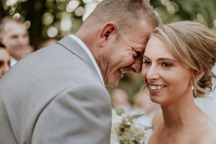 A close-up of the bride and groom's smiling faces, their foreheads touching. The groom is in profile, with the bride angled toward the camera.