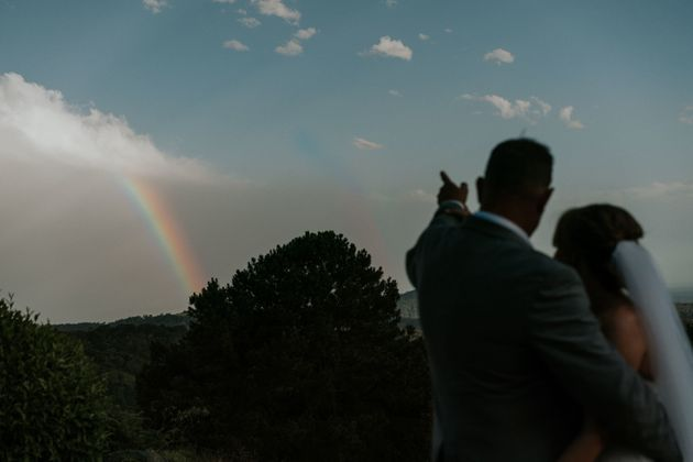 A silhouette shot of the bride and groom outdoors. The groom has his right arm wrapped around the bride...