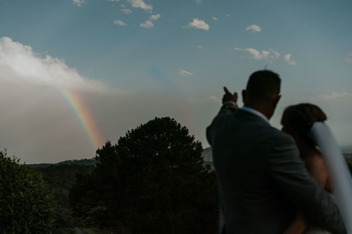 A silhouette shot of the bride and groom outdoors. The groom has his right arm wrapped around the bride as he points to a rainbow in the distance.