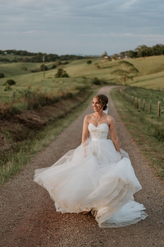 The bride, standing on a dirt road between green rolling hills, smiles as she plays with the skirt of...