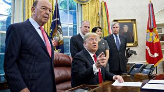 U.S. President Donald Trump, center, speaks before signing S. 3508, the Save Our Seas Act of 2018 as Wilbur Ross, U.S. commerce secretary, from left, Senator Dan Sullivan, a Republican from Arkansas, and Senator Sheldon Whitehouse, a Democrat from Rhode Island, listen in the Oval Office of the White House in Washington, D.C., U.S., on Thursday, Oct. 11, 2018. Trump on Wednesday said the 'Fed has gone crazy' with interest-rate increases this year and doubled-down on Thursday, blaming the nations 'out of control' central bank for a sixth straight day of losses in U.S. equities. Still, he said, 'I'm not going to fire him.' Photographer: Andrew Harrer/Bloomberg via Getty Images