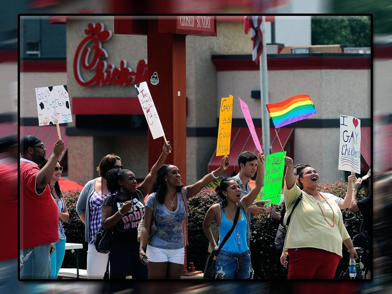 Gay rights activists holding signs during protest outside Chick-fil-a restaurant, Decatur, Georgia, on texture, partial graphic
