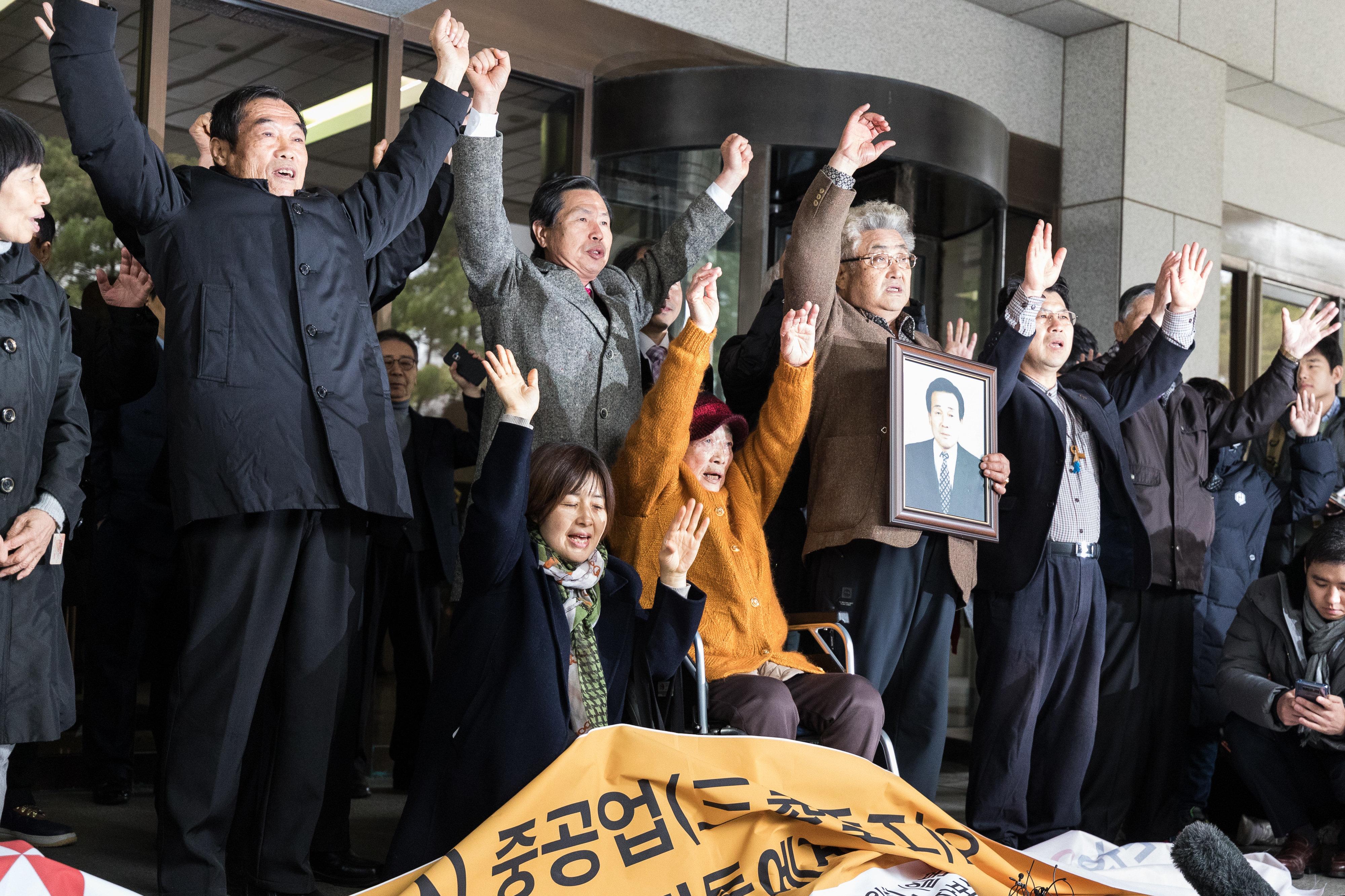 일제 강제징용 피해자 유가족들이 29일 서울 서초구 대법원에서 열린 일본 미쓰비시중공업 상대 손해배상 청구소송에서 이긴 뒤 만세를 외치고