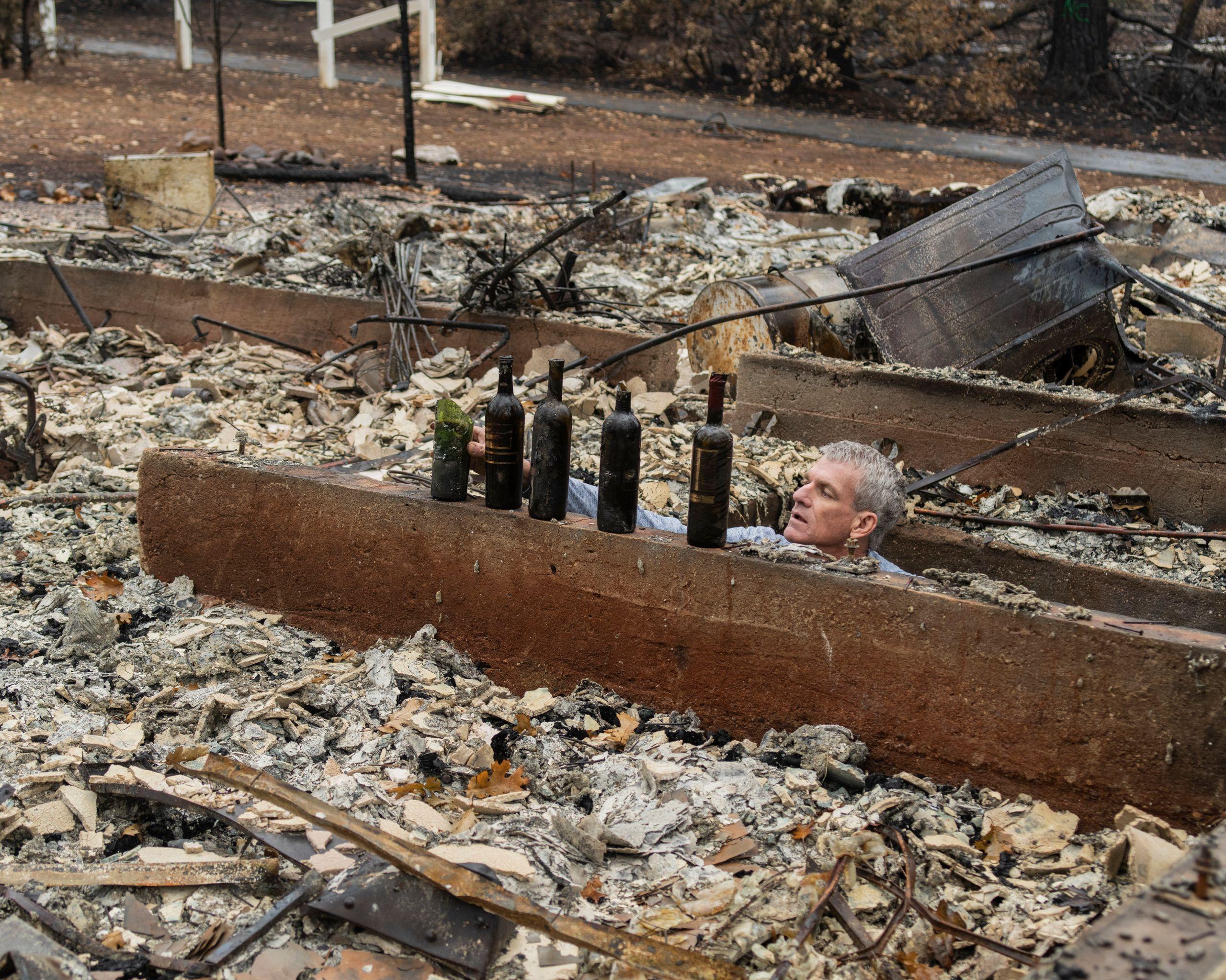 Robert Bean looking through his destroyed wine cellar.