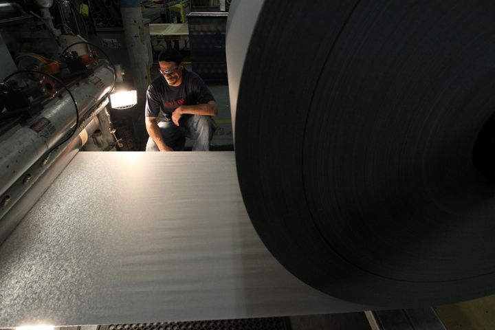Ryan Isherwood inspects the quality of the paper inside Onyx Specialty Papers in Lee, Massachusetts.
