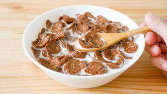Chocolate breakfast cereal in a white bowl on wooden table. Healthy breakfast concept.